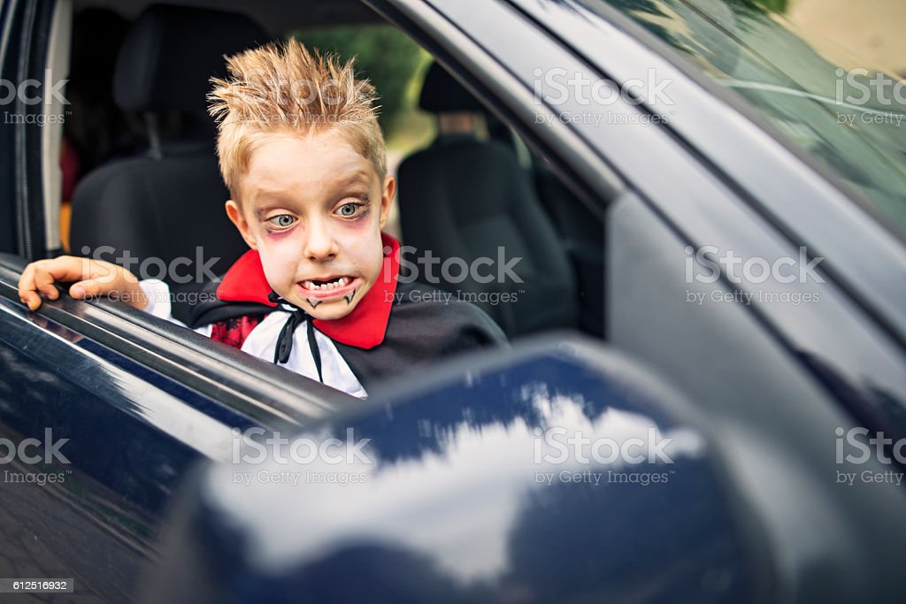 Little halloween boy practicing scary faces stock photo