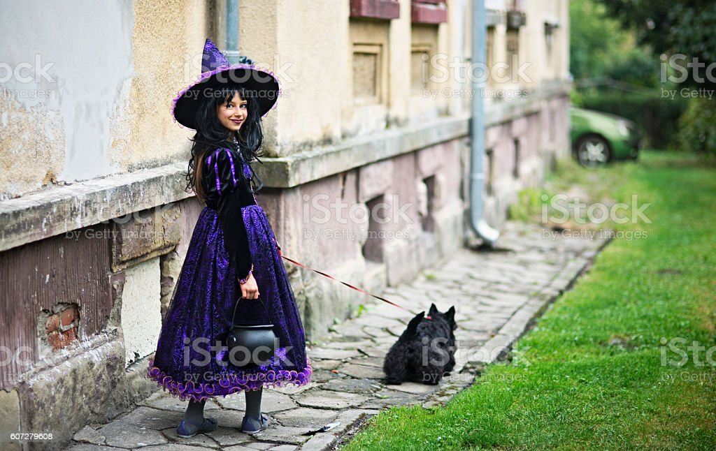 Little halloween witch walking with her familiar stock photo