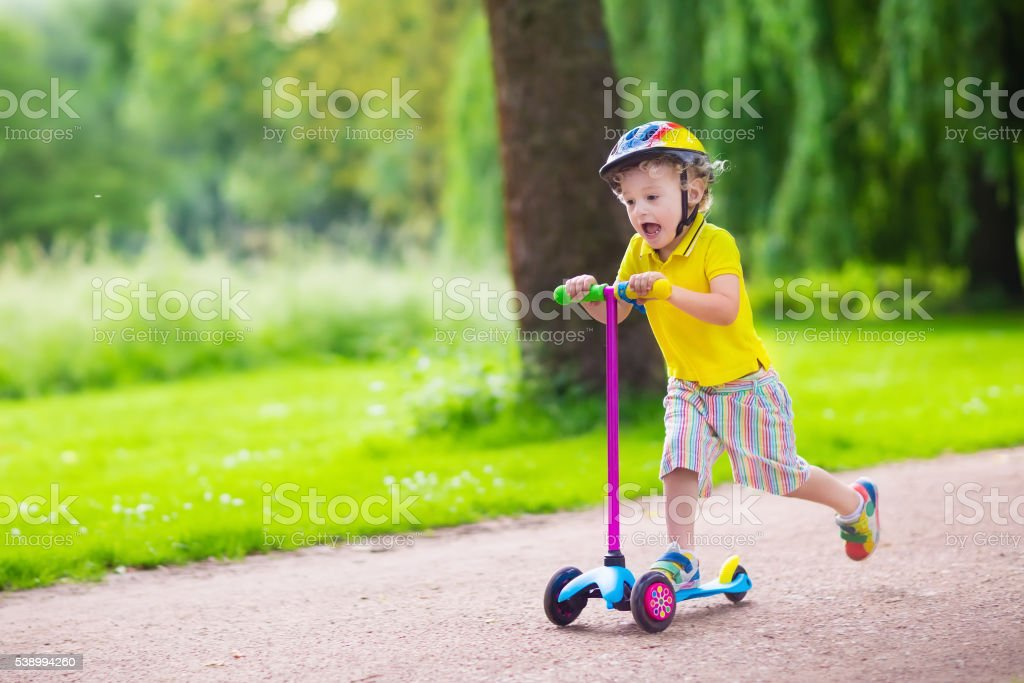 Little happy boy riding a colorful scooter stock photo