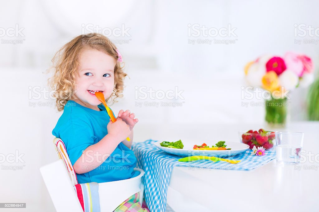 Little happy girl eating salad for lunch stock photo