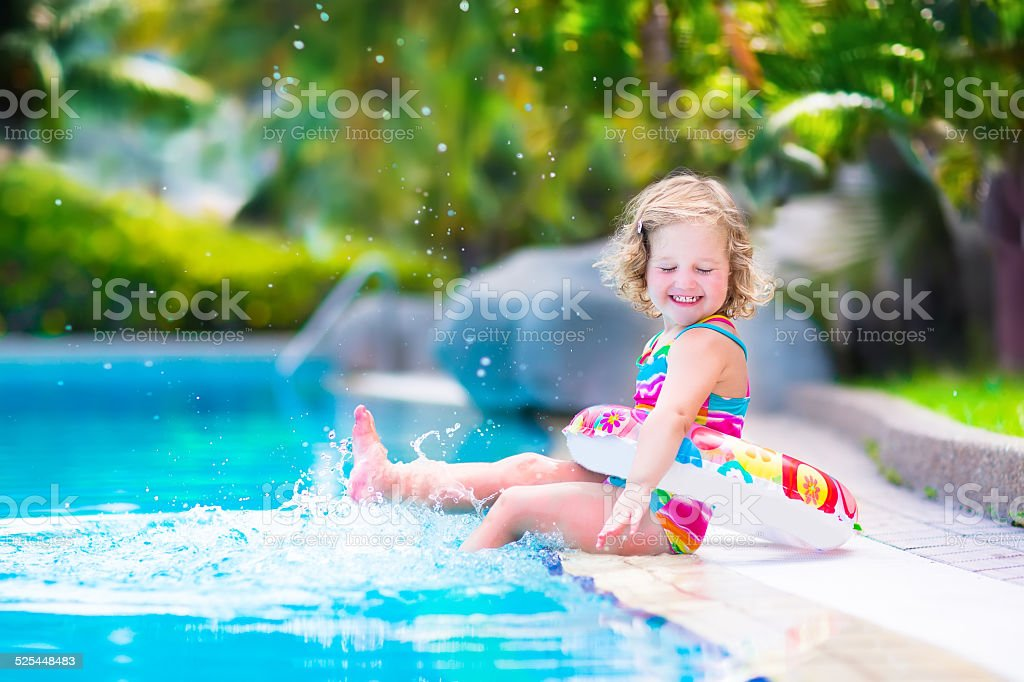 Little happy girl in a swimming pool stock photo