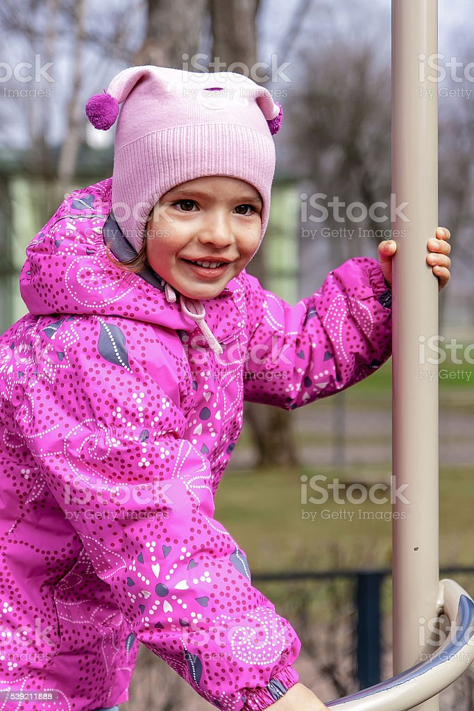 Little happy girl is playing on the kid's playground. stock photo