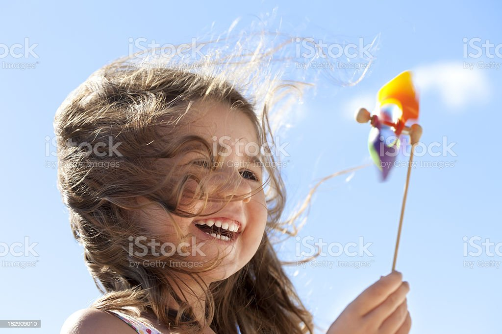 Little happy girl with pinwheel stock photo