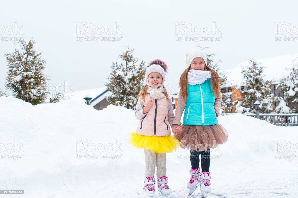Little happy girls skating outdoors in winter snow day stock photo