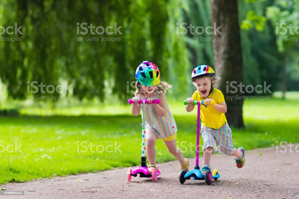 Little happy kids riding colorful scooters stock photo