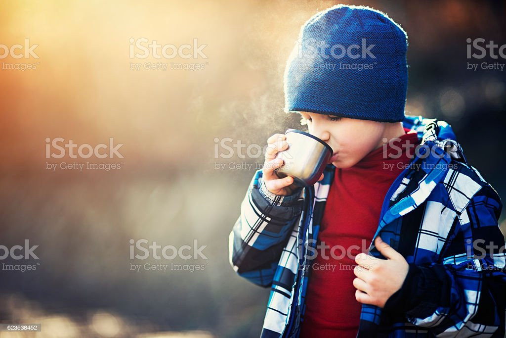 Little hiker drinking hot tea on sunny autumn day stock photo