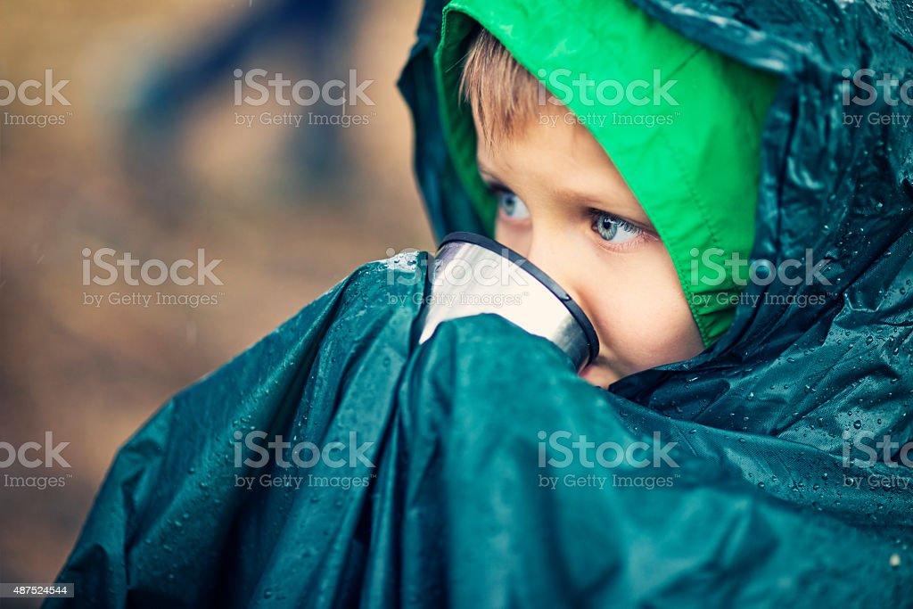 Little hiker drinking tea in the rain stock photo