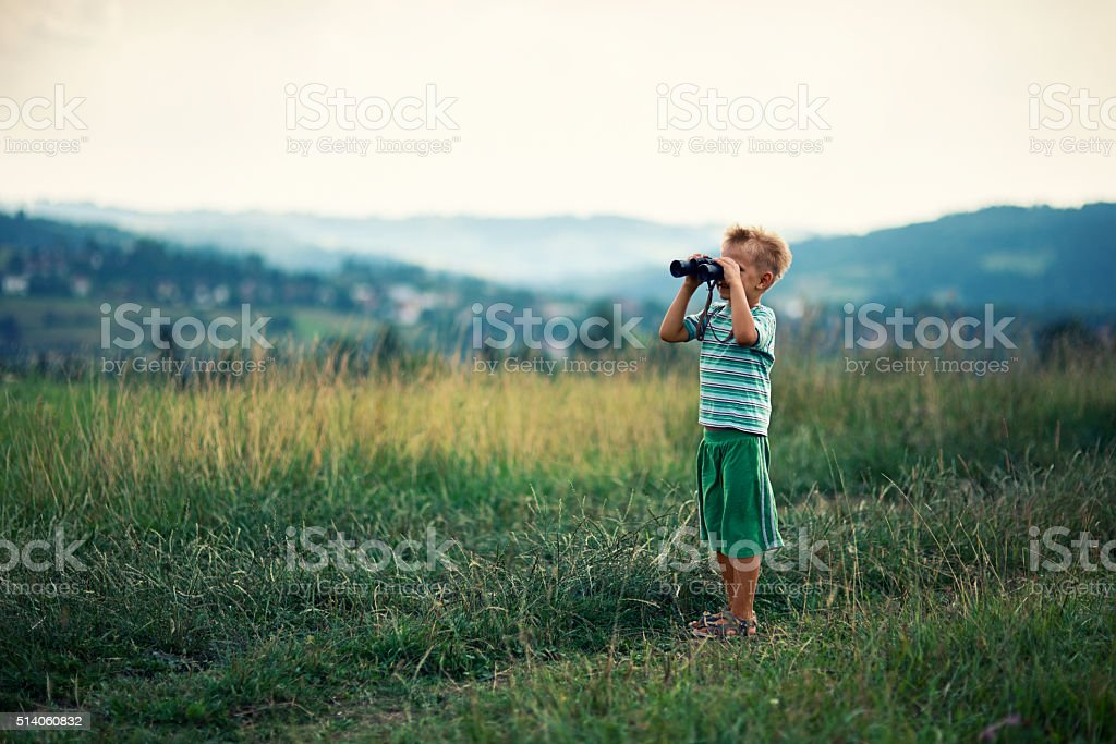 Little hiker looking at view with binoculars stock photo