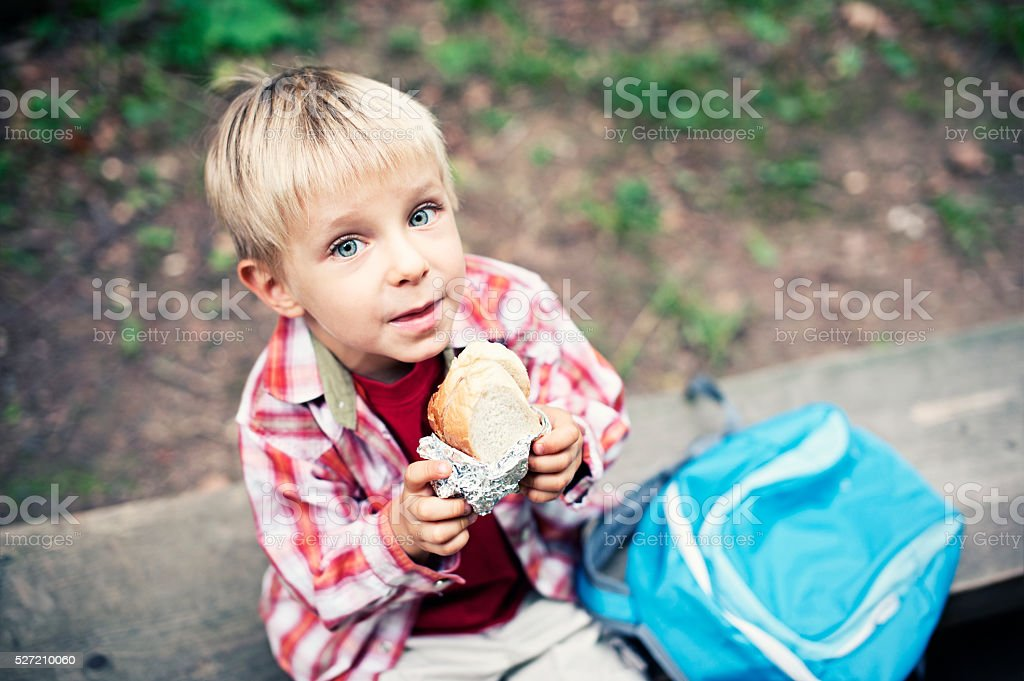 Little hiker resting and eating a sandwich stock photo