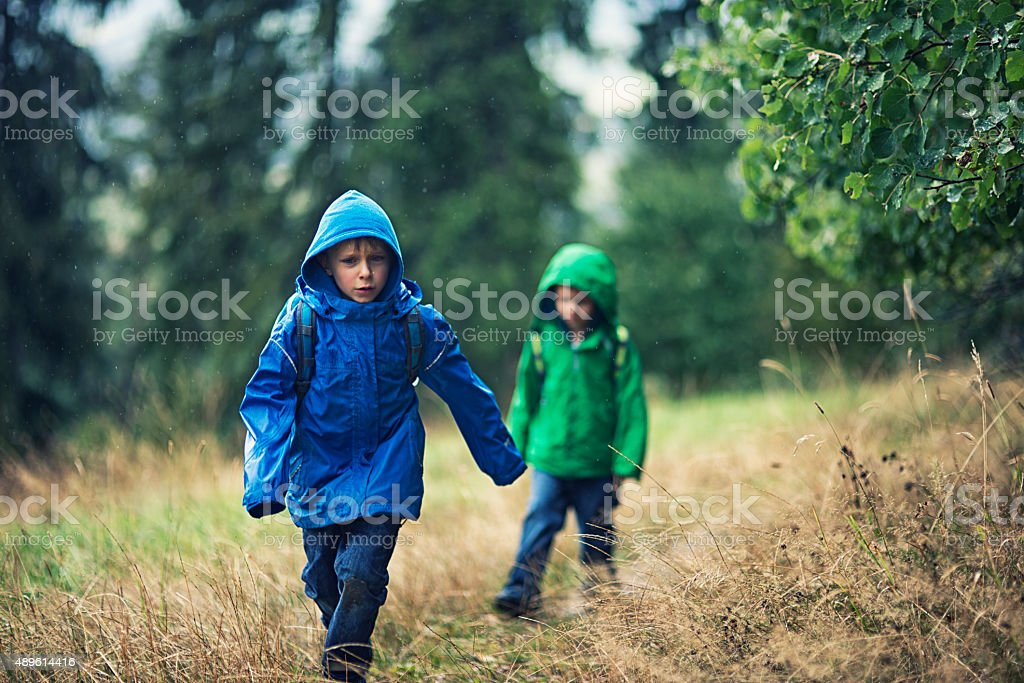 Little hikers in the rain stock photo