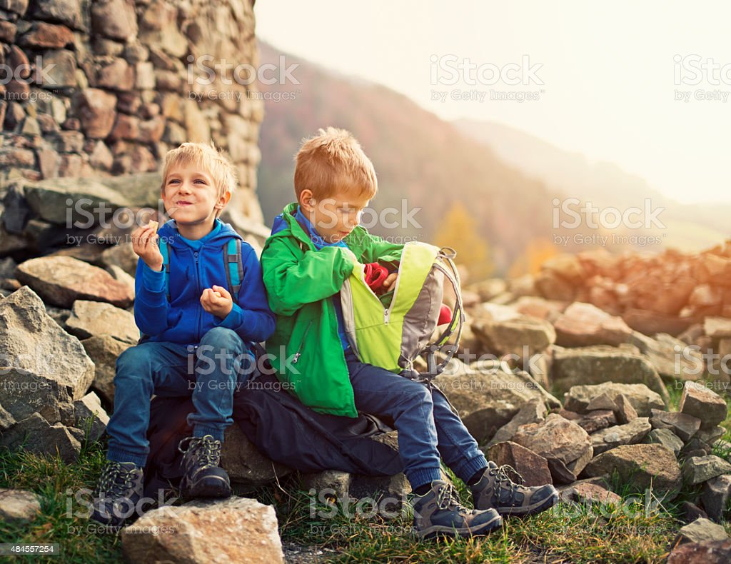 Little hikers resting and eating a snack stock photo