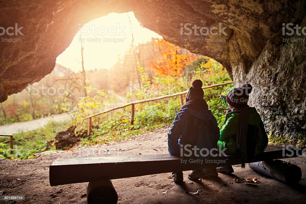 Little hikers resting in a cave stock photo
