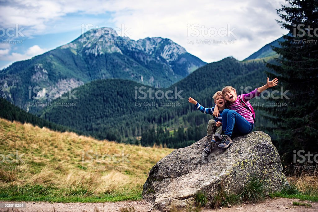 Little hikers resting on big stone and posing. stock photo
