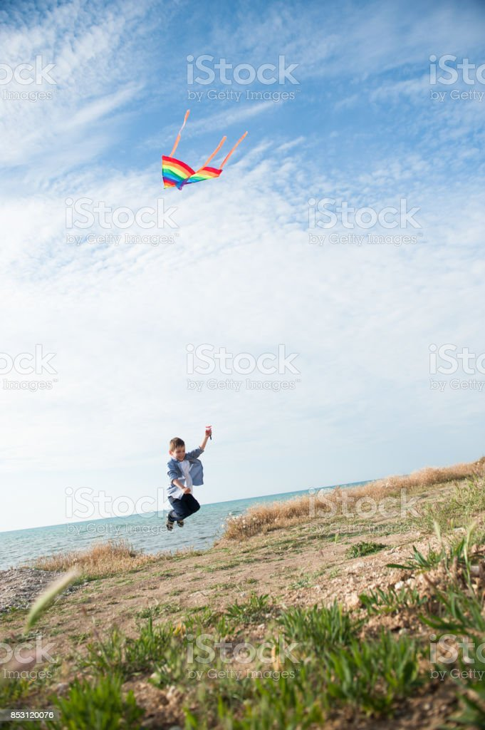 Little jumping boy holding a flying kite against the background of the sea and sky stock photo