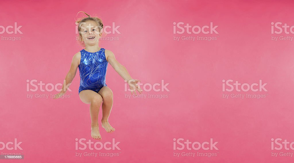 Little Jumping Gymnast on Pink Background stock photo