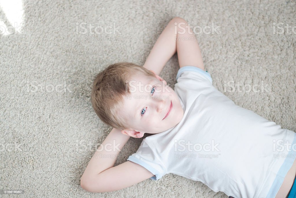 Little kid at home on a carpet stock photo