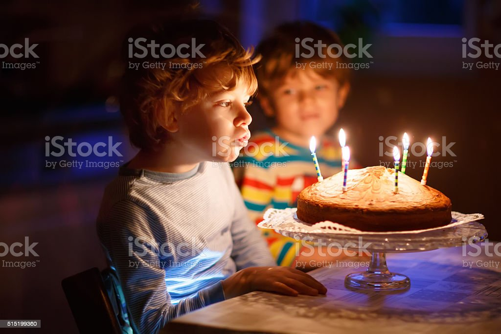 Little kid boy and brother blowing candles on birthday cake stock photo