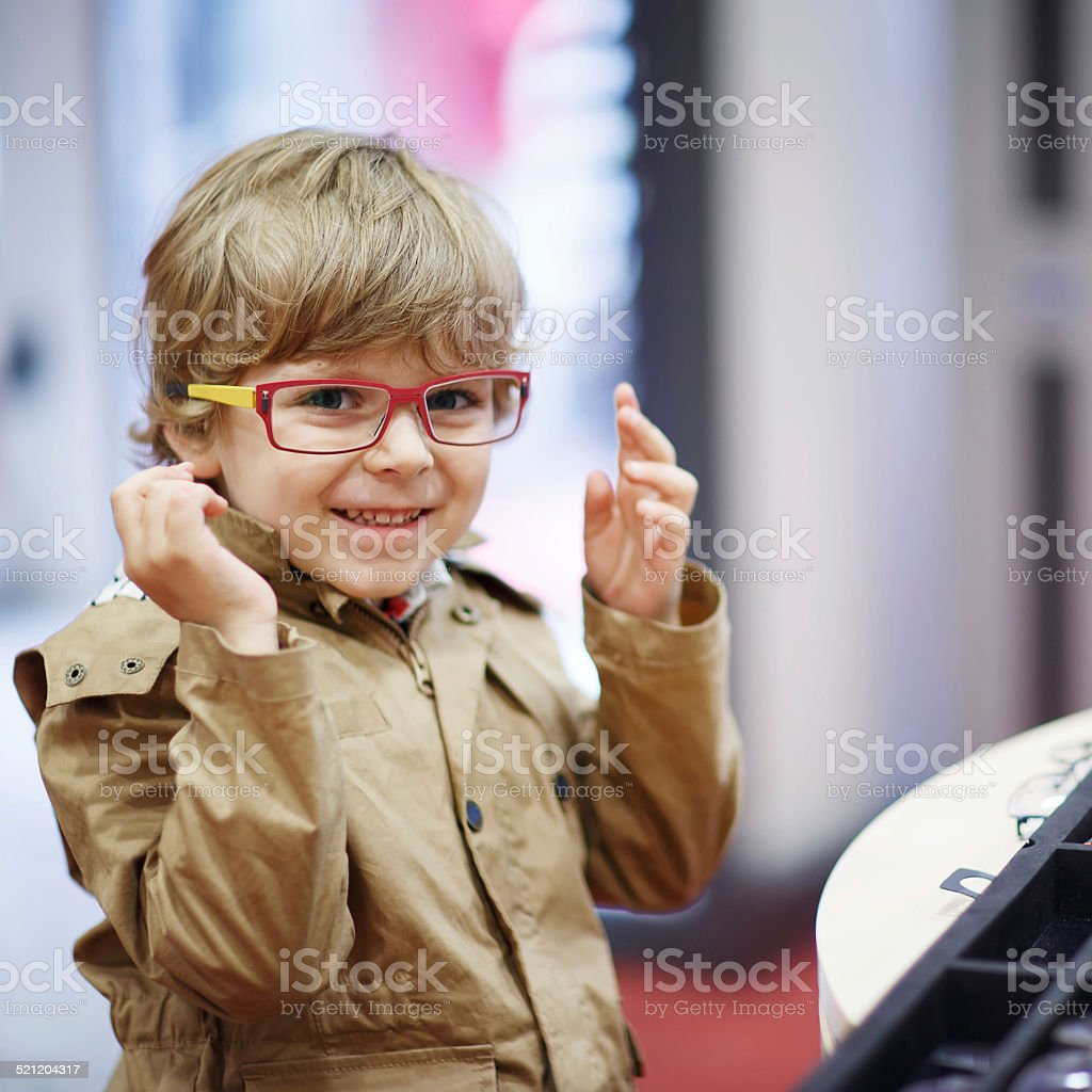 little kid boy at optician store during choosing new glasses stock photo