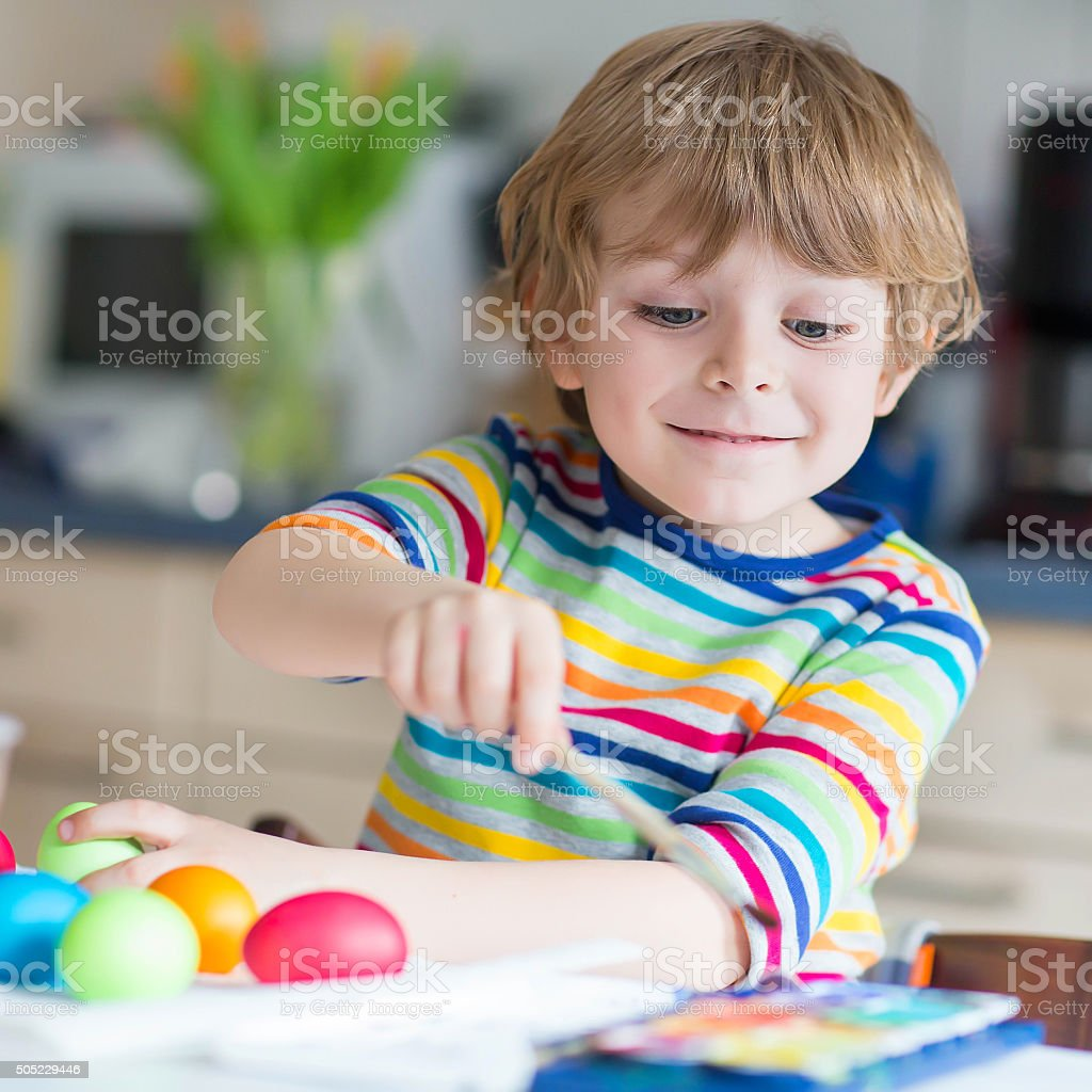Little kid boy coloring eggs for Easter holiday stock photo