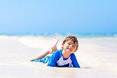 little kid boy having fun on tropical beach of Jamaica