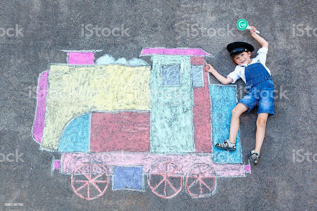 little kid boy having fun with train chalks picture stock photo