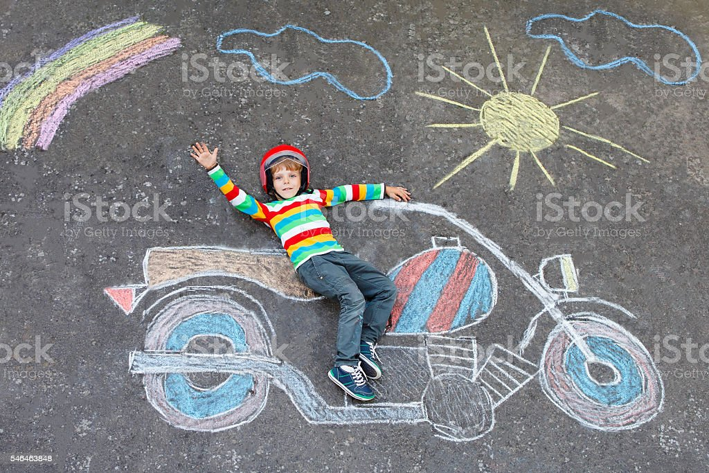 Little kid boy in helmet with motorcycle chalks picture stock photo