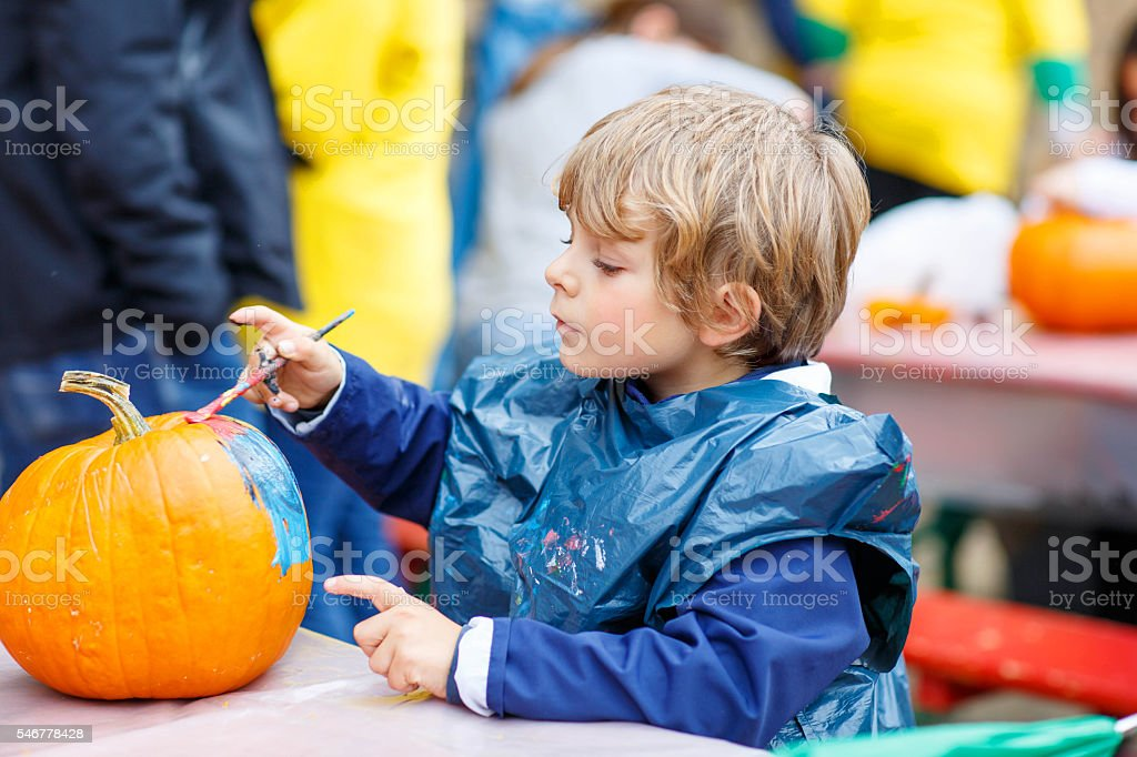 Little kid boy painting with colors on pumpkin stock photo