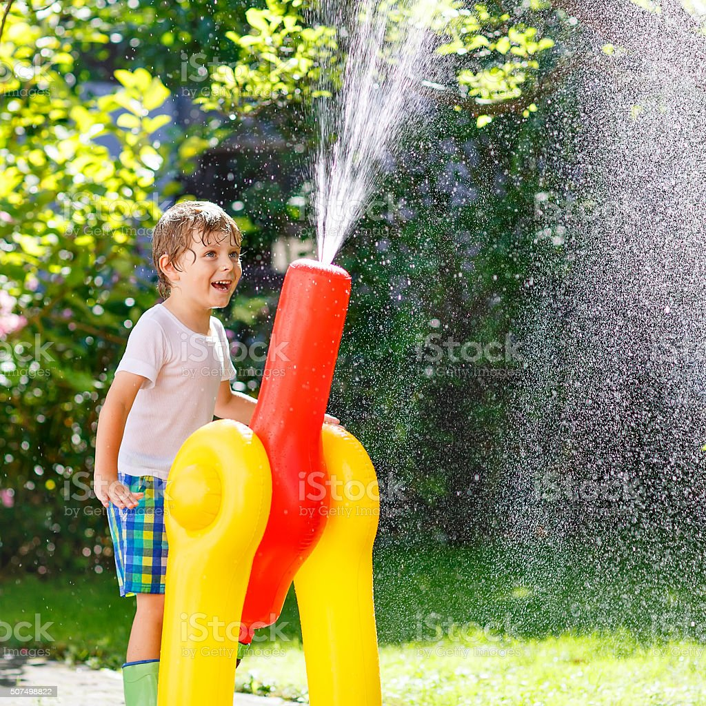 little kid boy playing  with a garden hose and water stock photo