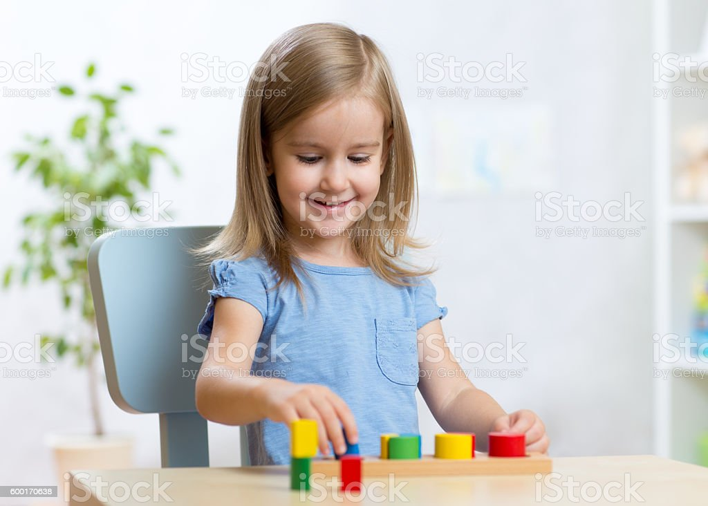little kid boy playing with educational toys stock photo