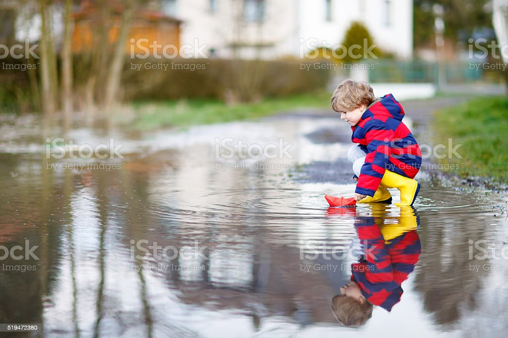 Little kid boy playing with paper boat by puddle stock photo