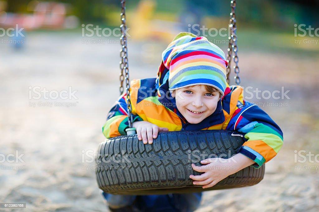 Little kid boy swinging on playground outdoors stock photo