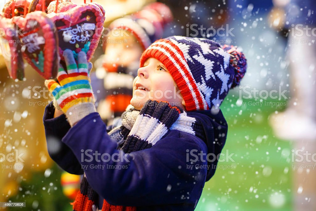 Little kid boy with gingerbread heart on Christmas market stock photo