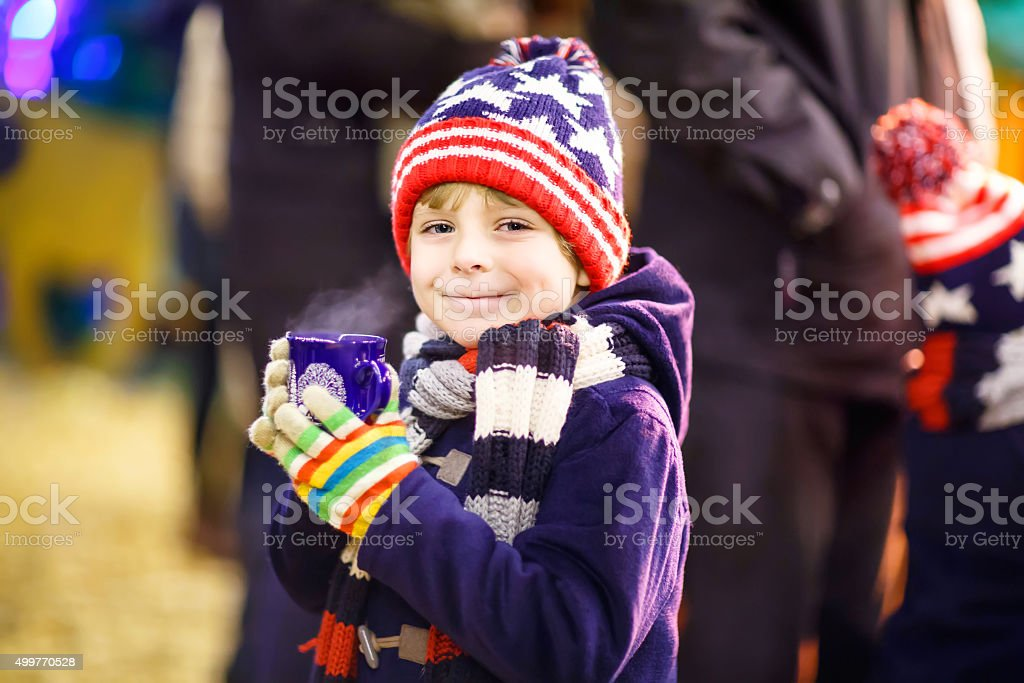 Little kid boy with hot chocolate on Christmas market stock photo