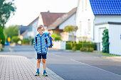 little kid boy with school satchel on way to school