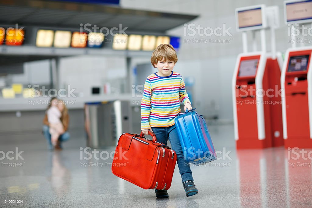 Little kid boy with suitcases on international airport stock photo
