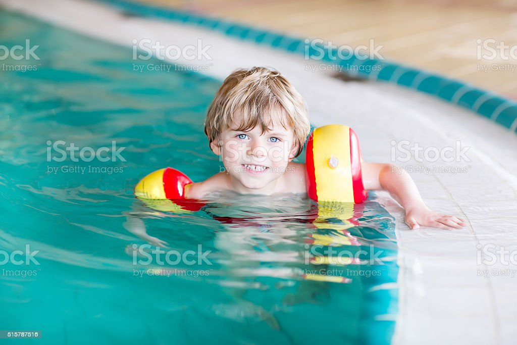 little kid boy with swimmies learning to swim indoor pool stock photo