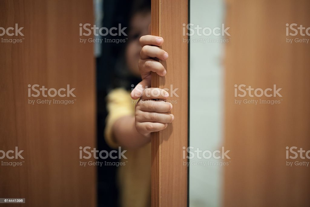 little kid playing hide and seek game; stock photo