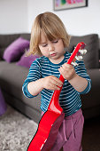 little kid playing red guitar