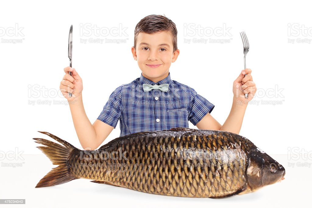 Little kid seated at table with a huge raw fish stock photo