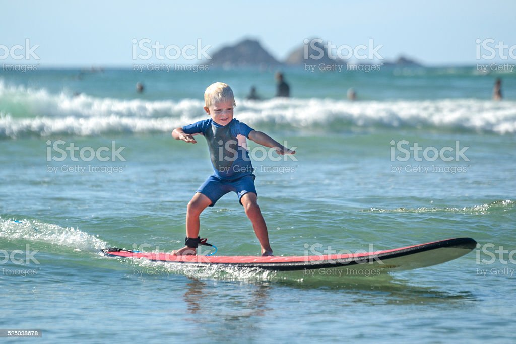 Little kid surfing stock photo