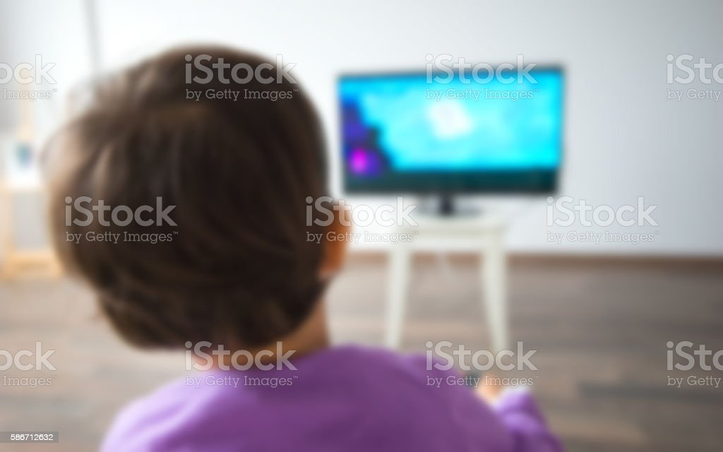 Little kid watching TV in the living room stock photo