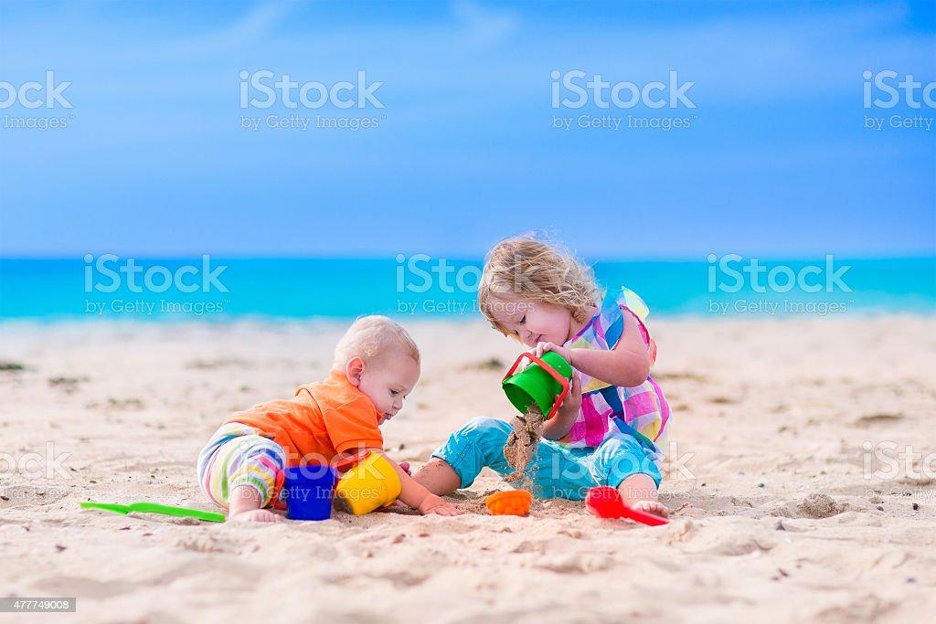 Little kids building a sand castle on a beach stock photo