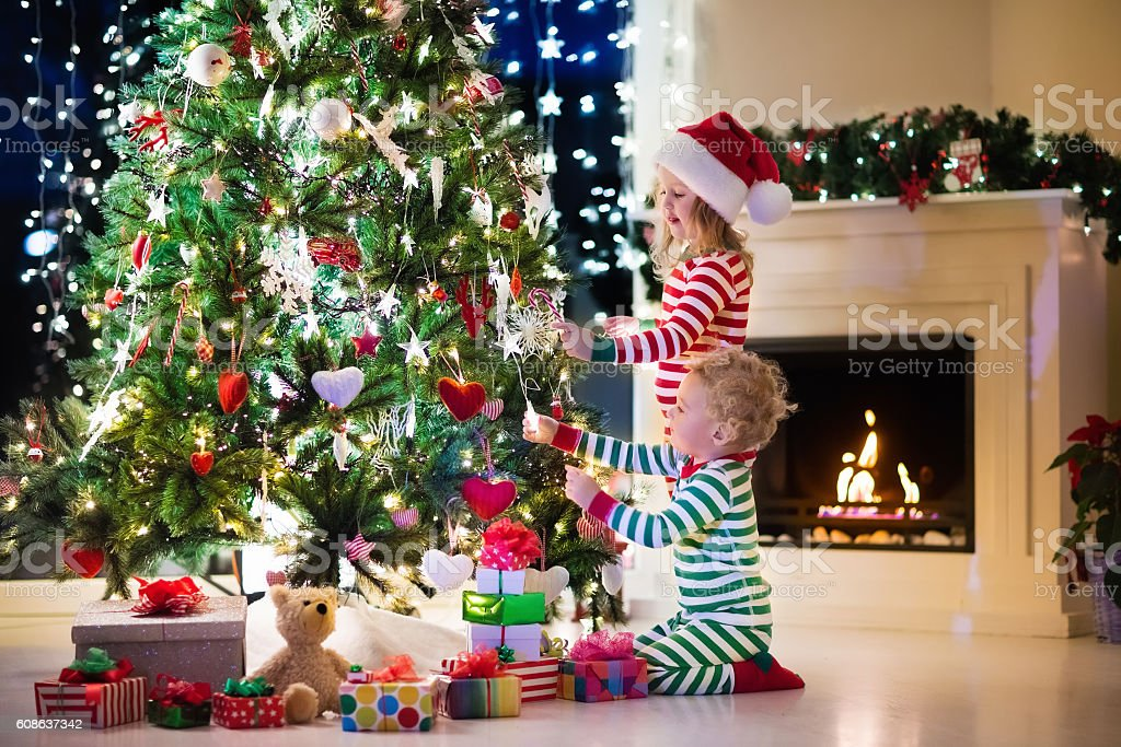 Kids Decorating For Christmas little kids decorating christmas tree stock photo 608637342 | istock