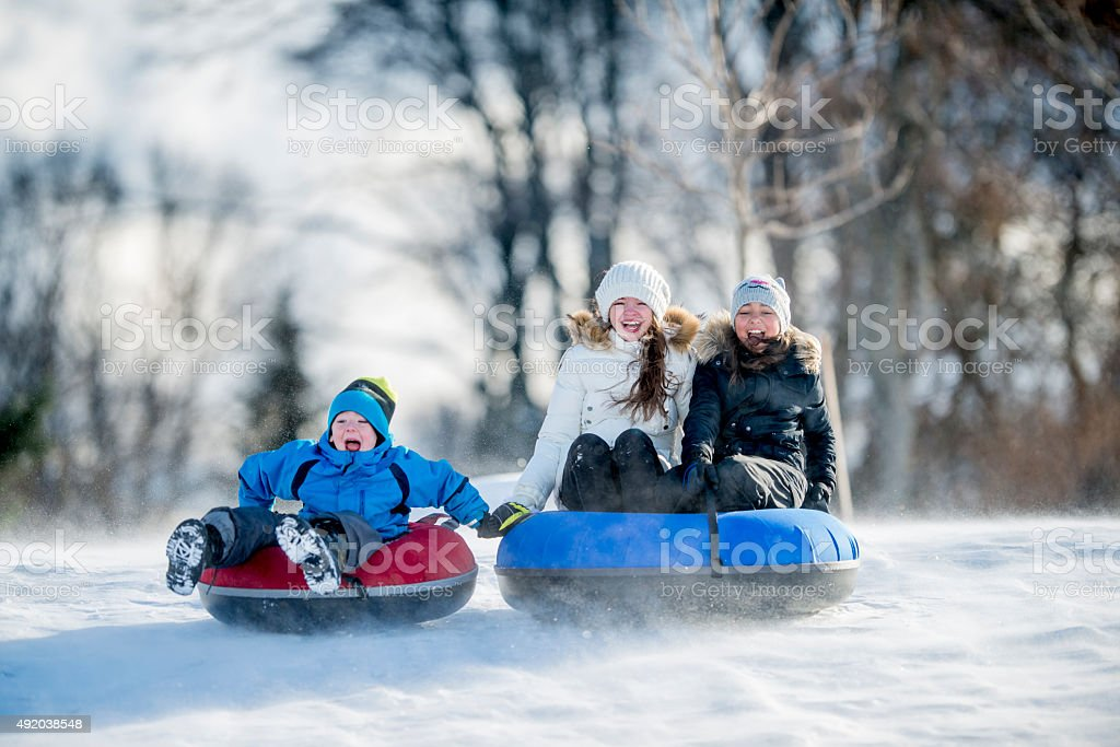 Little Kids Inner Tubing on a Sunny Winter Day stock photo