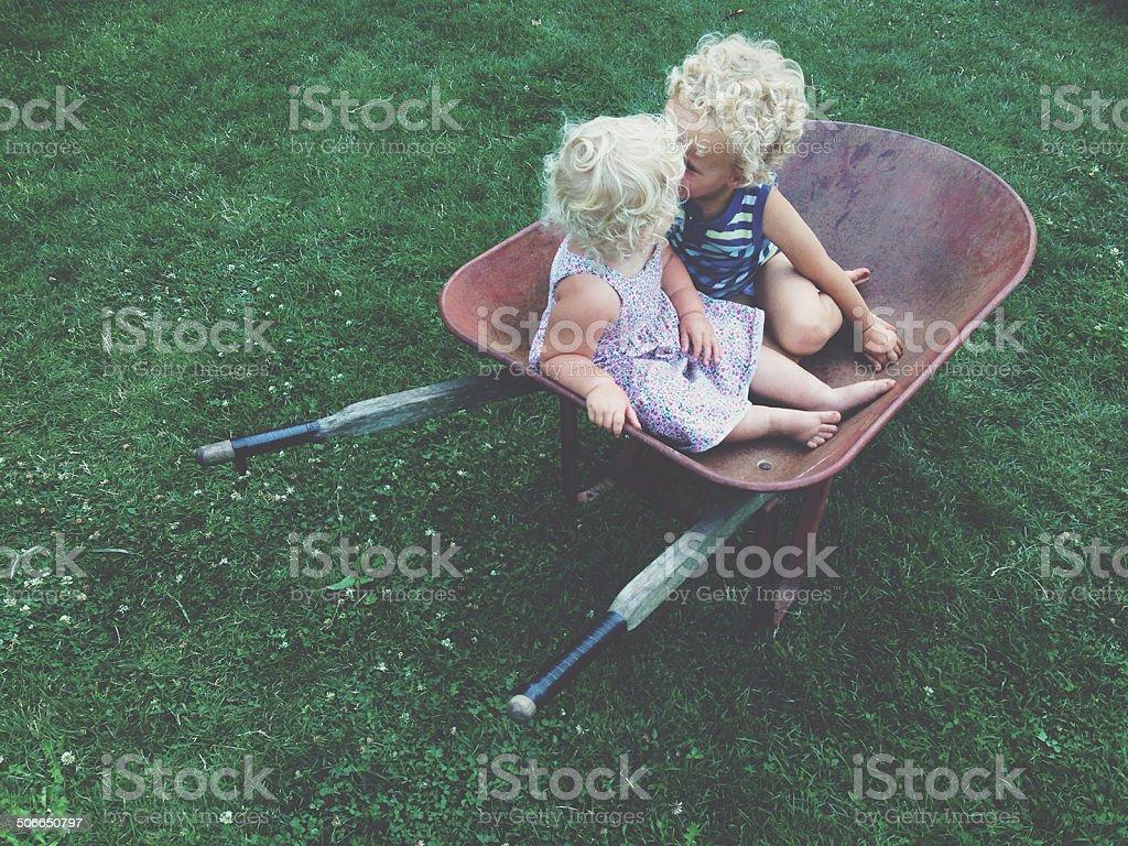 Little Kids Kissing in Wheelbarrow stock photo