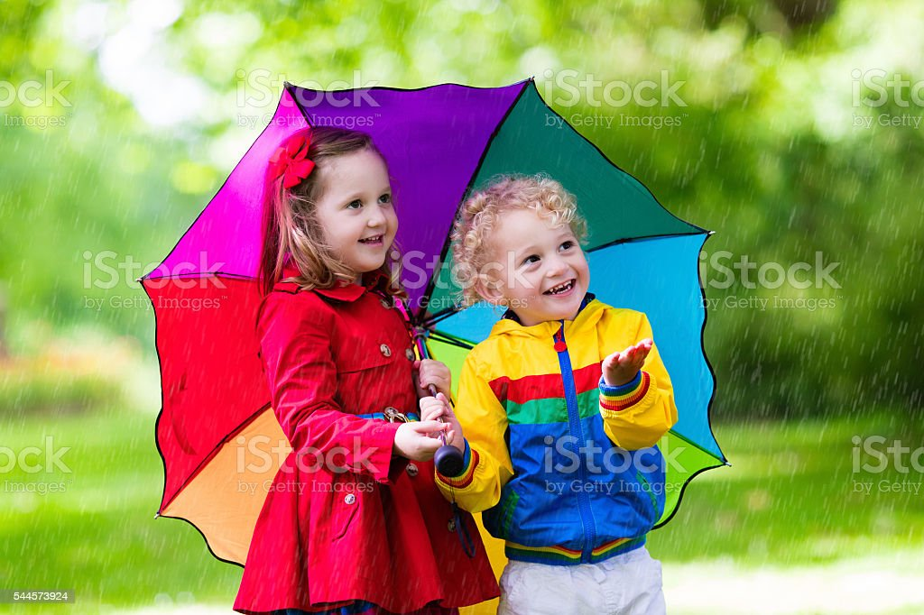 Little kids playing in the rain under colorful umbrella stock photo