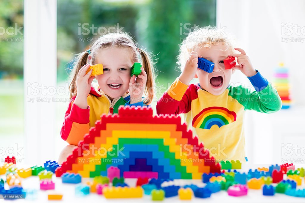 Little kids playing with colorful blocks stock photo