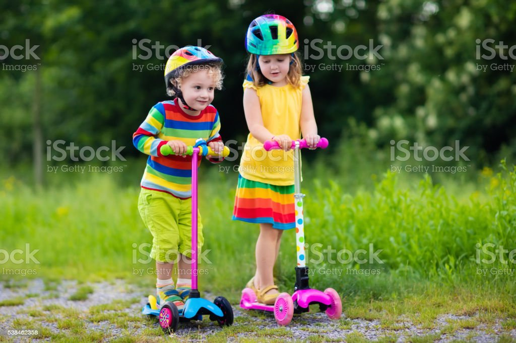 Little kids riding scooter in summer park stock photo