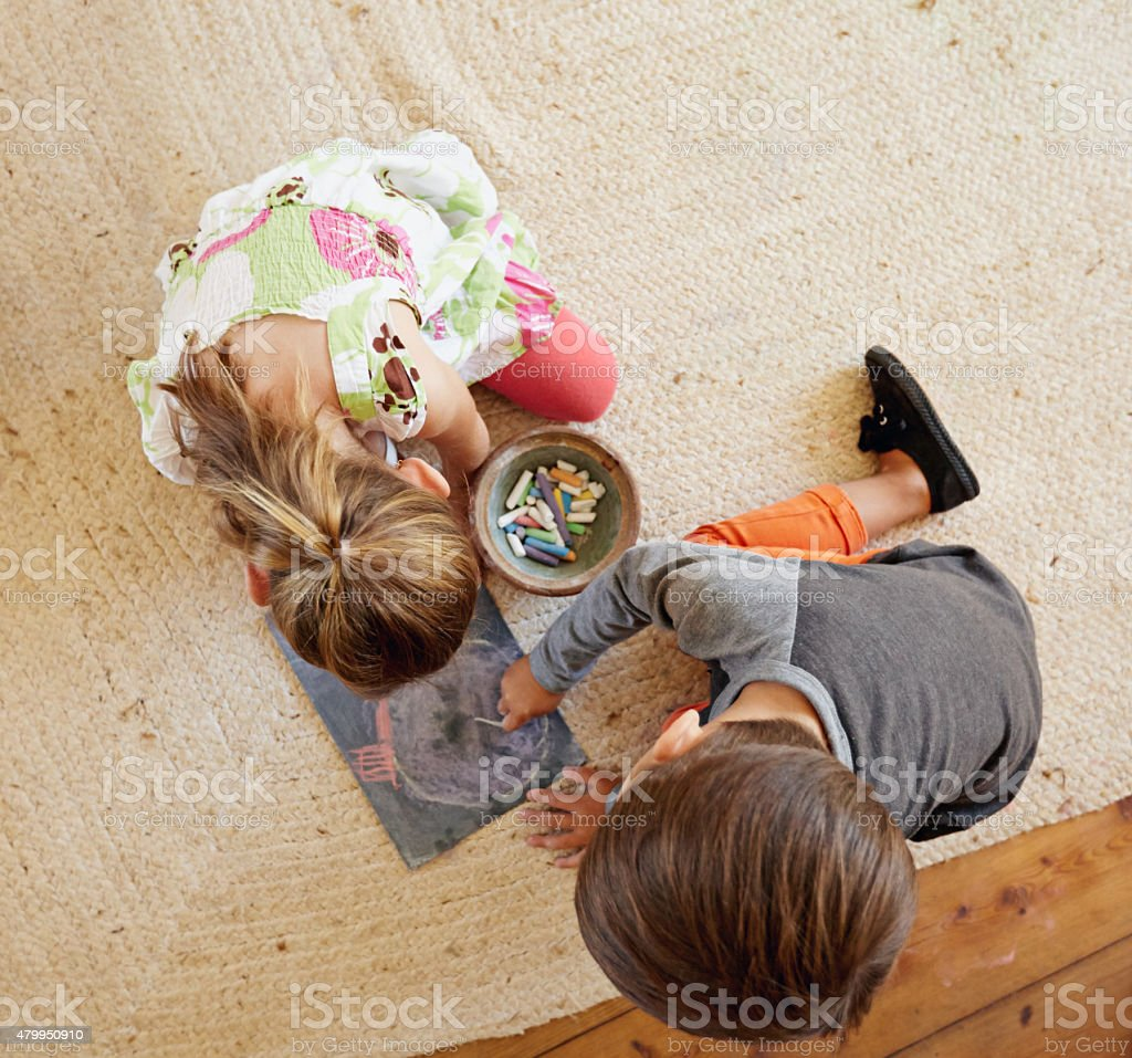 Little kids sitting on floor drawing with color chalks stock photo