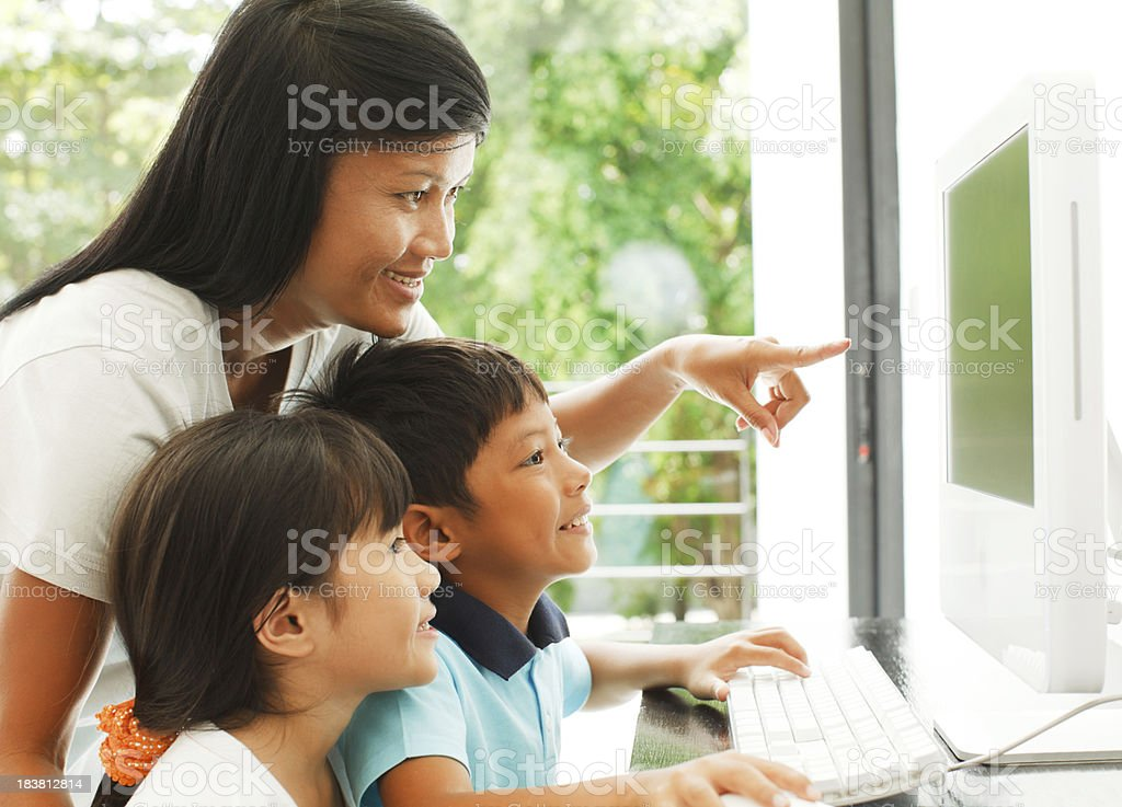 Little kids using laptop with their mother at home. stock photo
